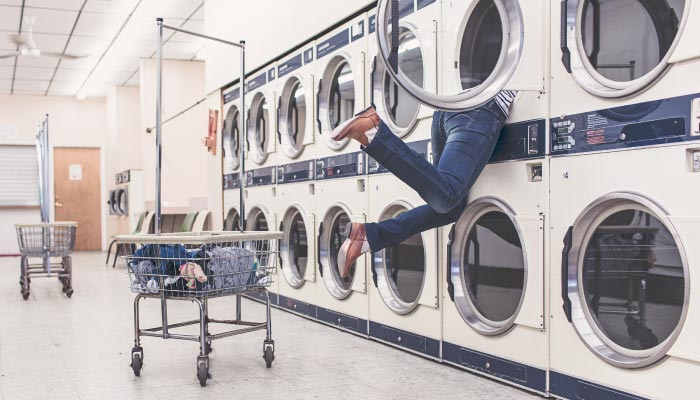 person half hanging out of washing machine at a laundromat