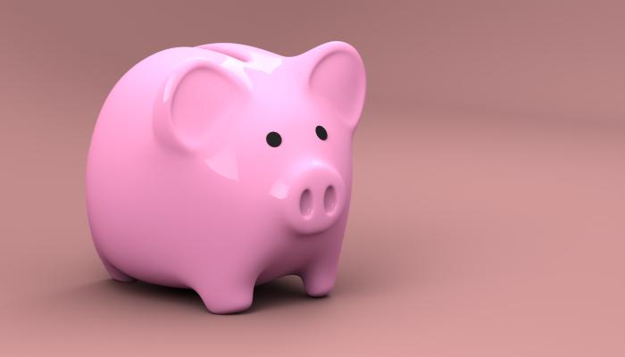 A bubblegum-pink piggy bank against a darker pink background