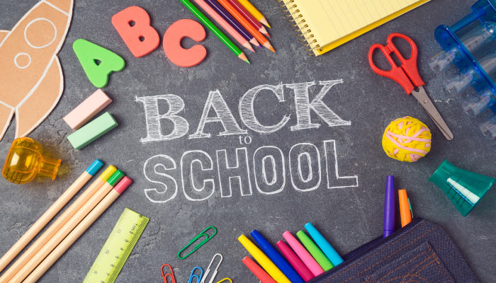 Aerial view of a black chalkboard surrounded by school supplies with Back to School written in the middle