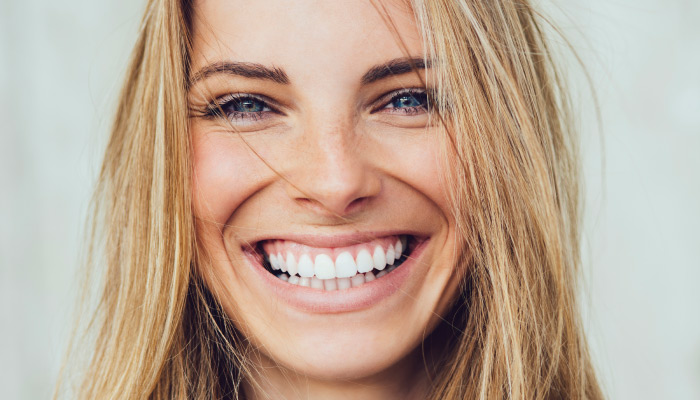 Closeup of a beautiful blonde woman smiling with bright white teeth because she uses an electric toothbrush