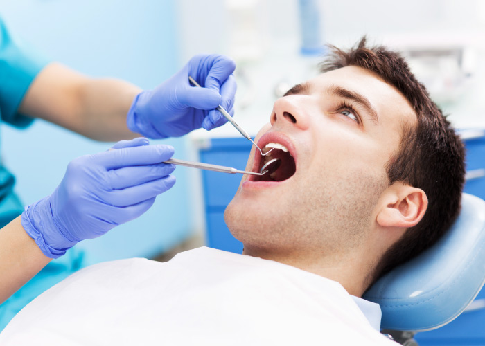 Brunette man sits in the dental chair with a white bib as a dentist looks into his mouth with dental tools