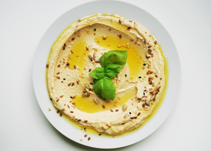 Aerial view of a plate of hummus topped with fresh basil