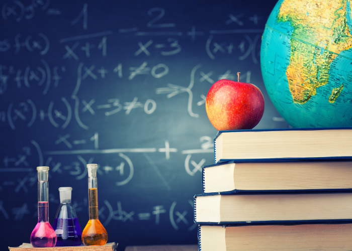 An apple and a globe sit on a stack of books next to colorful filled beakers in front of a chalkboard