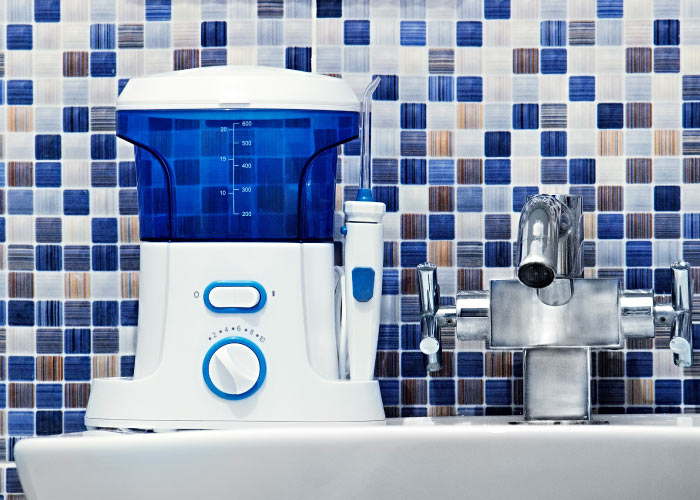 A blue and white water flosser sits on a bathroom sink in front of a blue and white mosaic wall