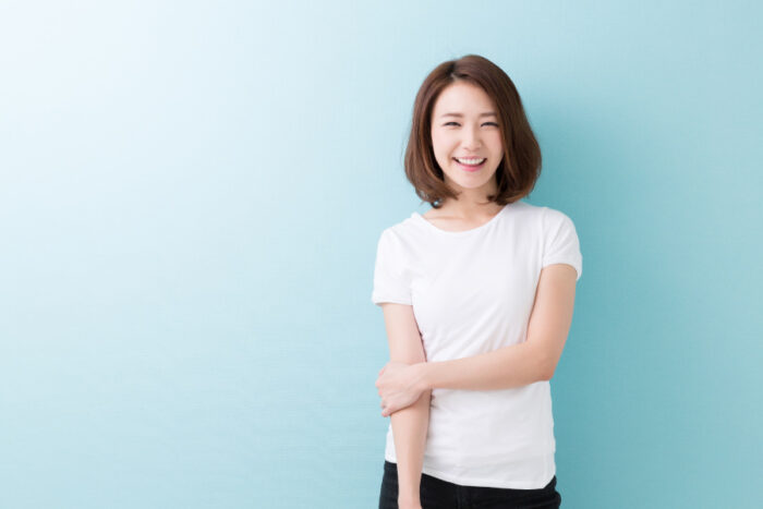Brunette woman in a white t-shirt smiles against a blue wall with dental implants