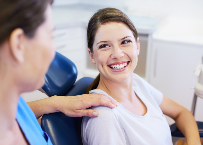 Brunette woman smiles before a tooth extraction in Westwood, KS