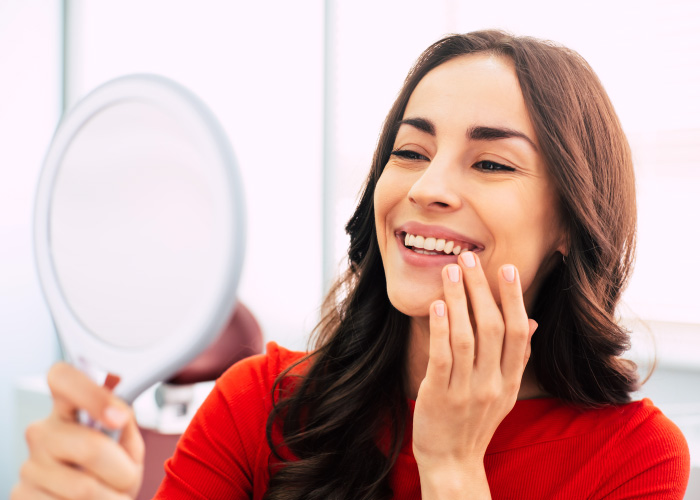 Brunette woman smiles into a handheld mirror after getting a dental implant
