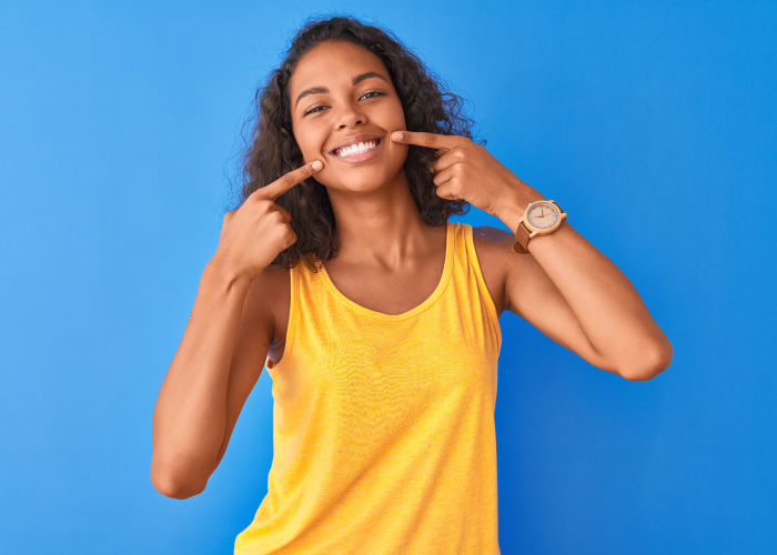 Brunette woman against a blue wall in a yellow tanktop points to her smile because of her great oral health
