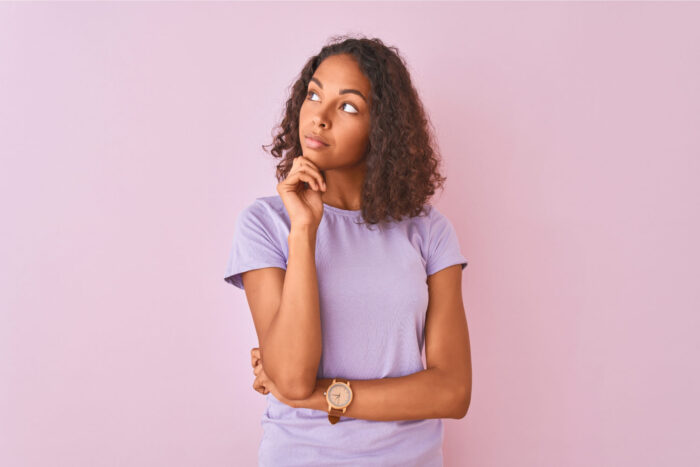 Brunette woman in a lavender shirt wonders why it is important to visit the dentist