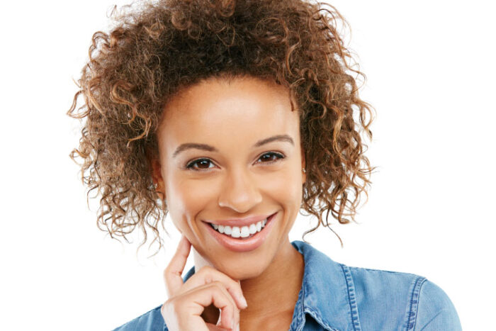 Pretty smiling woman with dark curly hair.