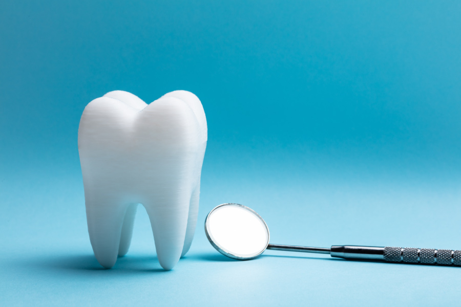 A white tooth next to a dental mirror against a blue background to indicate a tooth extraction