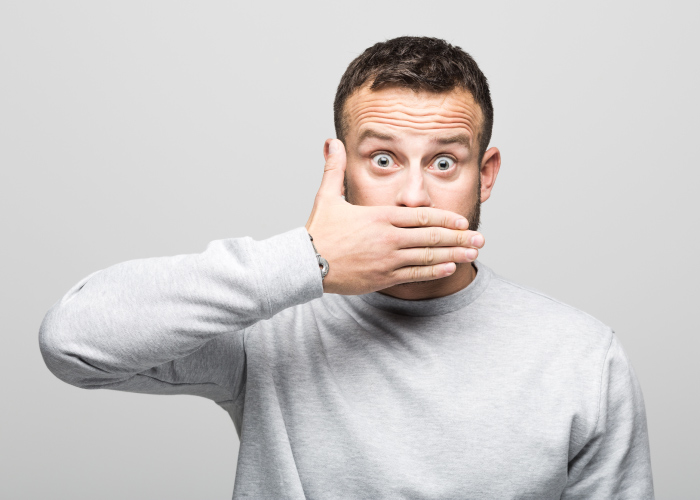 Brunette man coves his mouth in embarrassment due to bad breath in Westwood, KS
