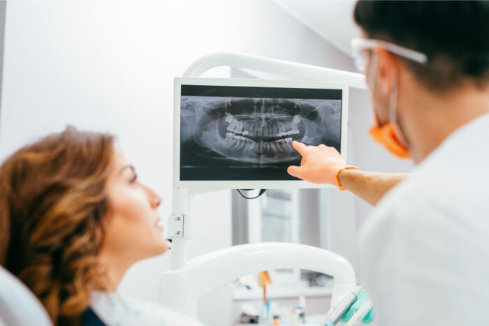 Dentist points at a panoramic X-ray and discusses its results with a female patient